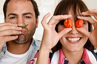 Close-up of a young woman covering her eyes with red chili peppers with a young man making mustache with a green chili pepper