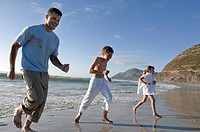 Mid adult man and his children running on the beach