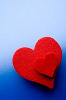 High angle view of two red hearts against a blue background