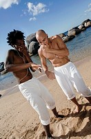 Young men wearing earbuds and dancing on the beach