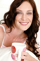 Portrait of a mid adult woman holding a coffee cup and smiling