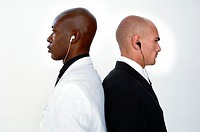 Side profile of two young men standing back to back and listening to music