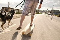 A man riding a skateboard while walking his dog