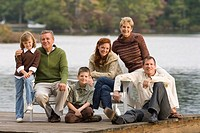 Three generations of family sitting by lake