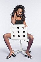 A woman sitting on a chair posing for the camera