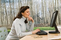 Woman with computer desk in woods