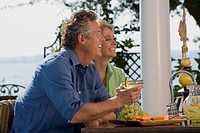 Couple sitting outdoors with cocktails