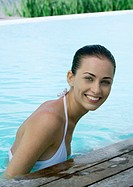 Young woman in pool, smiling at camera