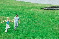 Couple walking across grass together