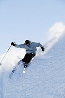 Downhill skier on steep slope