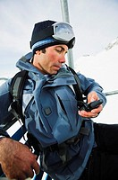 Man in ski gear using GPS device