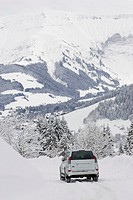 SUV by mountains in winter