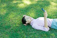 Businesswoman lying in grass, looking at cell phone