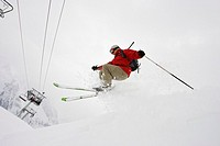 Downhill skier jumping off in mid-air