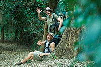Two hikers resting by tree, waving to camera