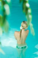 Young woman standing waist deep in pool, rear view