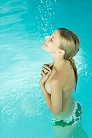 Young woman standing under spray of water in pool, covering bare chest