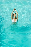 Young woman standing with arms up and eyes closed in pool (thumbnail)