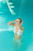 Young woman standing in pool under spray of water (thumbnail)