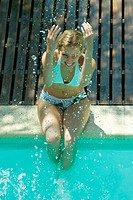 Young woman sitting on edge of pool, splashing water