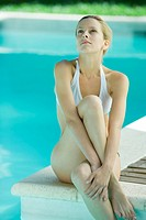 Young woman sitting on edge of pool, legs crossed, looking up