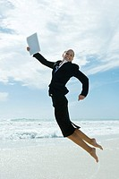 Businesswoman jumping in air on beach, smiling at camera