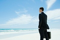 Businessman standing on beach, holding briefcase, facing ocean