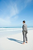 Barefoot businessman standing on beach, facing ocean