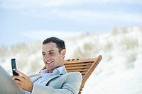 Businessman sitting in lounge chair on beach, looking down at cell phone, smiling