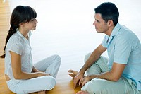 Man and woman sitting on floor, face to face