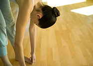 Woman doing standing forward bend, partial view