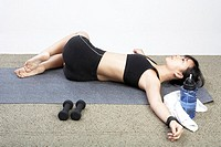 Young woman lying down with arms outstretched on mat in gym