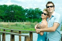 Couple standing by footbridge, man holding woman in his arms, both wearing sunglasses