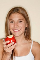 Teenage girl 13-15 holding apple, smiling, close-up, portrait
