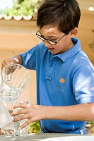 Boy 8-10 pouring water from jug in garden
