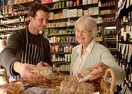 Male shop assistant showing groceries to female customer, smiling
