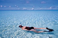 Mature woman snorkelling in expanse of clear water