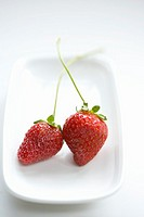 Two strawberries on serving tray, elevated view