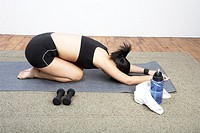 Young woman on all fours with face down on mat in gym