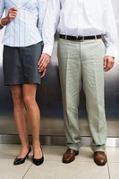 Business couple holding hands in lift, low section