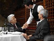Waiter shaking senior businessman´s hand in restaurant