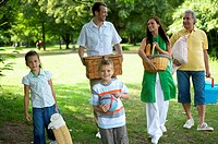 Multi-generational family carrying picnic things in park, smiling