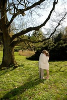 Teenage couple 15-17 standing under tree wrapped in blanket