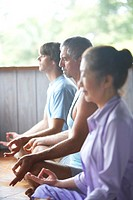 Three people meditating in yoga class, side view