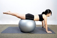 Young woman balancing on exercise ball in gym