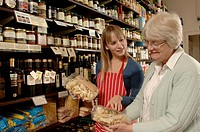 Female shop assistant showing pasta to female customer in delicatessen