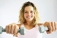 Young woman exercising with hand weights, portrait