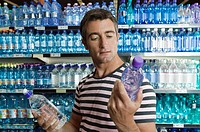 Man choosing between two bottles of water in supermarket