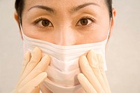 Female dentist adjusting surgical mask, portrait, close-up