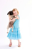 Girl 5-6 holding pug, portrait